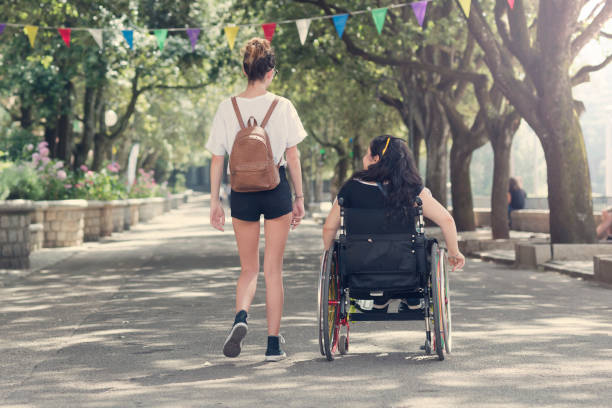 Jeune femme qui marche à côté de son amie en fauteuil roulant