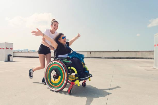 Jeune femme qui pousse le fauteuil roulant de son amie