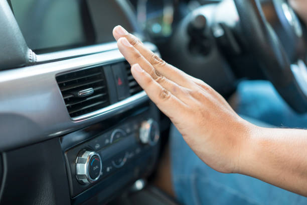 Main qui teste la clim d'une voiture