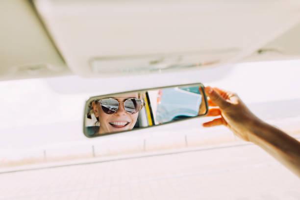 Reflet d'une jeune femme en lunette de soleil dans le rétroviseur d'une voiture