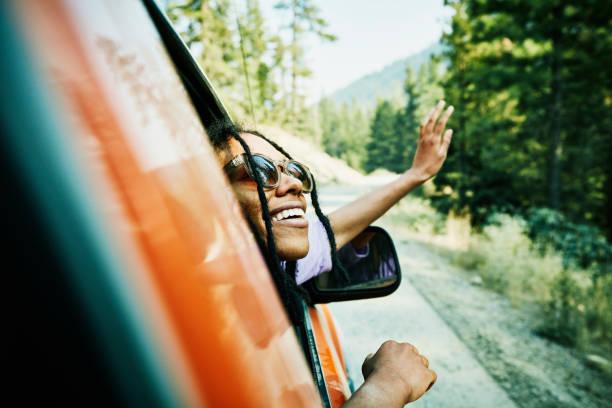 Femme qui sort sa tête par la fenêtre d'une voiture
